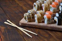 一套的详细的射击日本寿司卷和他们的用途筷子的一个设备,位于木切开的b 图库摄影
