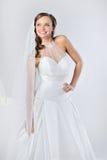 一套空白婚礼礼服的美丽的微笑的女孩 图库摄影