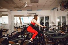 一套红色体育衣服的可爱的妇女在健身房,乘坐在速度固定式自行车 r 库存图片