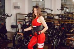 一套红色体育衣服的可爱的妇女在健身房,站立与一个瓶水在固定式自行车附近 r 图库摄影