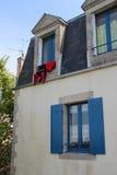 一套红色保温潜水服烘干在房子(法国)的窗口 免版税库存图片