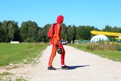 一套红色衣服的一位伞兵在跃迁的一架飞机上去 库存照片