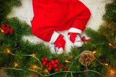 一套红色衣服的圣诞老人腿婴孩在杉木针圣诞节花圈与欢乐装饰的 免版税库存照片