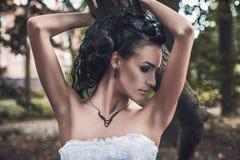 一套美丽的深色的新娘婚礼礼服的画象在公园 免版税库存图片