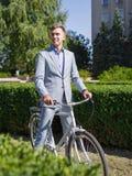 一套美丽的衣服的一个人在自行车乘坐在街道下 免版税图库摄影