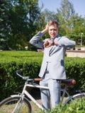 一套美丽的衣服的一个人在自行车乘坐在街道下 免版税库存图片