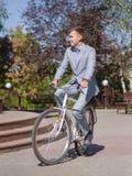 一套美丽的衣服的一个人在自行车乘坐在街道下 免版税库存照片