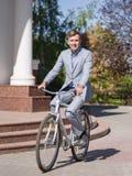 一套美丽的衣服的一个人在自行车乘坐在街道下 库存照片