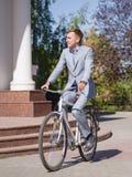 一套美丽的衣服的一个人在自行车乘坐在街道下 库存图片