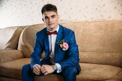 一套美丽的衣服的一个微笑的人坐长沙发 他在一件白色衬衣、链扣、一套蓝色衣服和a穿戴了 免版税图库摄影