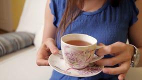一套蓝色衣服的一个女孩坐长沙发和喝茶考虑某事的 中国黏土托起木饮用的糖表茶的茶壶二 股票录像