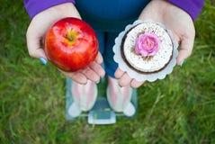 一套蓝色衣服的一名肥胖妇女在站立在桃红色运动鞋的透明玻璃标度并且选择一个红色大苹果或蛋糕 库存照片