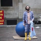 一套蓝色衣服的男性演员和在科文特花园的黄色橡胶狗展示表现 图库摄影