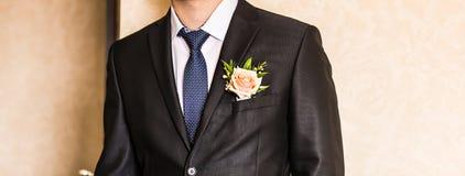 一套衣服的人与钮扣眼上插的花 库存照片