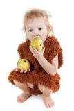 一套衣服的小滑稽的穴居人的男孩与肮脏的面孔吃苹果的 库存照片