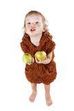一套衣服的小滑稽的穴居人的男孩与肮脏的面孔吃苹果的 免版税库存照片