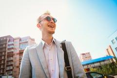一套衣服的年轻人反对城市背景 免版税图库摄影