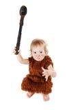 一套衣服的滑稽的男孩穴居人与拿着轴的肮脏的面孔 免版税图库摄影