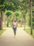 一套西装的美丽的妇女在城市公园的胡同 免版税库存图片