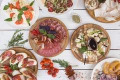 一套许多开胃菜:鲱鱼,炸薯条,乳酪,香肠,三明治,肉, ?herry蕃茄,调味料,绿色 免版税库存照片