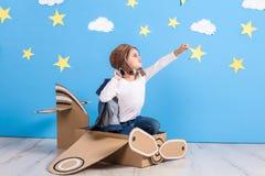 一套试验` s服装的小孩女孩是使用和作梦在云彩的飞行 免版税库存图片