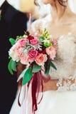 一套豪华婚礼礼服的新娘与拿着婚礼花束的鞋带由玫瑰做成 库存照片