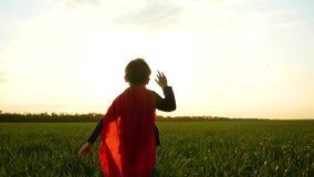 一套超级英雄服装的一个孩子,在一个红色斗篷,横跨绿草的奔跑反对日落的背景 股票视频