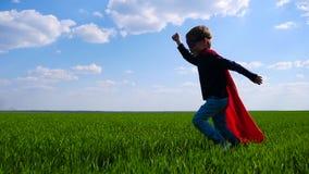 一套超级英雄服装的一个愉快的孩子在一件红色雨衣通过一个绿色领域,对抢救的仓促跑 股票录像
