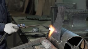 一套运作的衣服的铁匠拿着一盏焊接用喷灯 股票视频