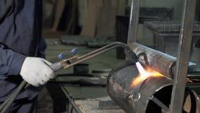 一套运作的衣服的铁匠拿着一盏焊接用喷灯 影视素材