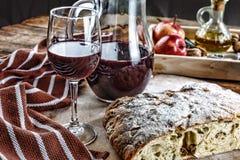 一套酒的快餐 一杯红葡萄酒、绿色地中海橄榄、熏火腿、蒜味咸腊肠、烟肉和年迈的乳酪在土气b 免版税库存照片