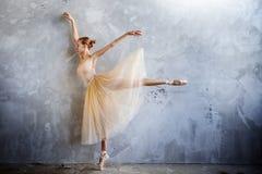 一套金黄色的跳舞的服装的年轻芭蕾舞女演员在顶楼演播室摆在 免版税库存图片