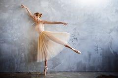 一套金黄色的跳舞的服装的年轻芭蕾舞女演员在顶楼演播室摆在 免版税图库摄影