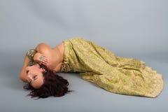 一套金黄服装的年轻美丽的肚皮舞表演者 免版税库存照片