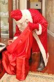一套长的明亮的衣服和手套的圣诞老人从大红色袋子得到礼物 库存照片