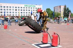一套防火衣服的一位消防员跑并且转动大橡胶把消防竞争,白俄罗斯,米斯克, 08引入 08 2018年 免版税库存照片