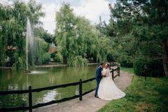 一套黑暗的衣服的新郎拥抱一件豪华的白色礼服的女孩 恋人在有池塘和喷泉的公园走 免版税库存图片