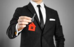 一套黑衣服的一个人把握关键到房子 钥匙圈红色 免版税库存照片