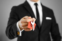 一套黑衣服的一个人把握关键到房子 钥匙圈红色 图库摄影
