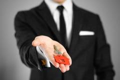 一套黑衣服的一个人把握关键到房子 钥匙圈红色 免版税库存图片