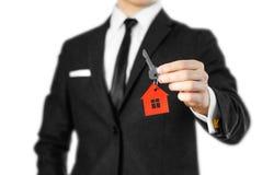 一套黑衣服的一个人把握关键到房子 钥匙圈红色 库存图片