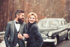 一套黑衣服的新郎与妇女室外在减速火箭的汽车附近 免版税图库摄影