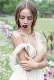 一套轻的米黄婚礼礼服的美丽的柔和的女孩新娘与在他的嘴的一朵花在一个美丽的花园,温暖一个的夏天里 免版税库存照片