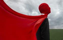 一套黑衣服的人与一块红色布料 库存图片