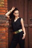 一套黑衣服的美丽的妇女在木und砖backgro 库存照片