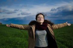一女孩感觉喜悦和愉快在与云彩的绿色领域 库存照片