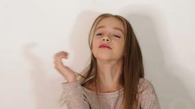 一女孩的画象一件米黄毛线衣的在白色背景的演播室 股票视频