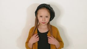 一女孩的画象黑帽会议、黑礼服和棕色夹克的在演播室 股票录像