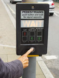 一女性手按鹈鹕横穿的控制按钮在英国 图库摄影