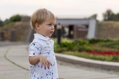 一好奇或惊奇的逗人喜爱的男婴stayibg的画象在公园夏日 情感,鬼脸,惊奇,孩子 免版税库存图片